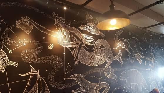 이 벽화는 사이렌이 별자리 생물들 사이로 별을 붓는 걸 묘사했다. [사진 Starbucks Melody]