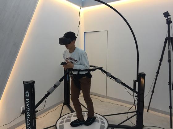 '사용자 움직임 반응형 트레드밀 시스템'에서 체험객이 직접 몸을 움직이며 가상 현실 속을 걸어다니는 체험을 하고 있다.[사진 가상증강 현실 융복합센터]