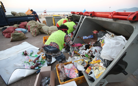 부산 해운대해수욕장에서환경미화원들이 백사장에서 수거한 많은 쓰레기를 분리수거 하고 있다.송봉근 기자
