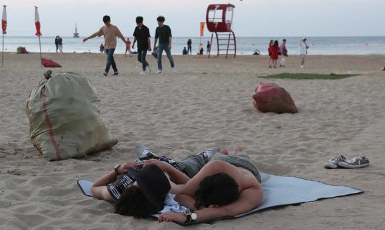 지난 5일새벽 부산시 해운대해수욕장에서 밤새 술을 마시고 노숙하고 있는 피서객들. 송봉근 기자