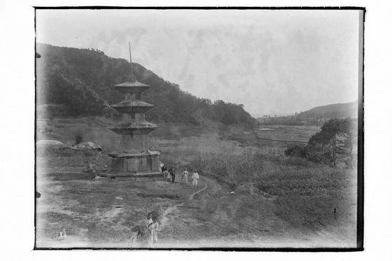 1920~30년대 경북 경주 감은사지 삼층석탑. 주민이 석탑에 앉아있다. [사진=경주세계문화엑스포]
