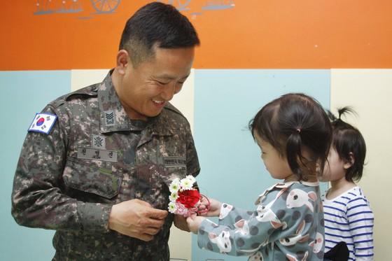 은평천사원 엔젤스헤이븐의 아이가 전병진 상사에게 카네이션을 달아주고 있다.[사진 육군5기갑여단]