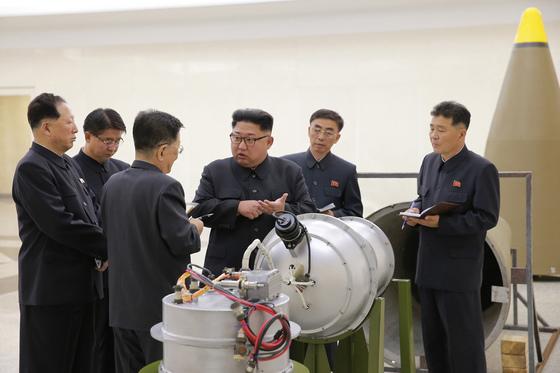 핵무기연구소를 방문한 김정은이 수소탄 탄두 모형앞에서 연구소 관계자와 이야기하고 있다.[조선중앙통신]