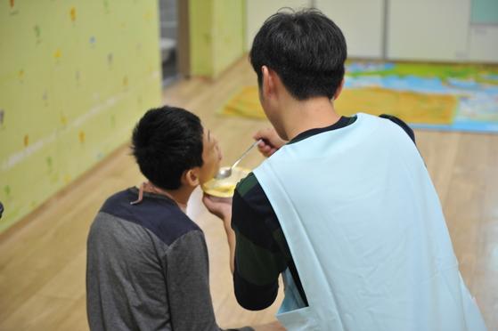 김준영 기자가 한사랑마을에서 지내는 장애인의 식사를 돕고 있다. [사진 초록우산어린이재단]