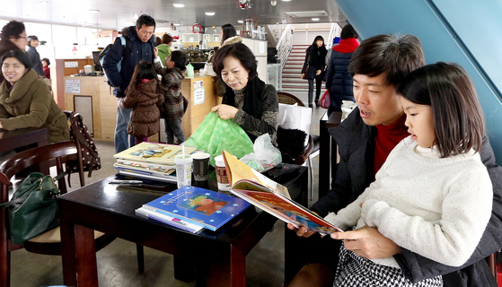 """장애인 특수학교인 서울 강남구 '밀알학교'의 북카페를 이웃 주민들이 이용하고 있다. 1990년대 이 학교가 들어서려 하자 상당수 주민들은 """"집값 떨어진다""""고 반발하면서 갈등이 커졌다. 하지만 체육관과 미술관 등을 개방한 이 학교는 '주민 사랑방'이 됐다. [중앙포토]"""