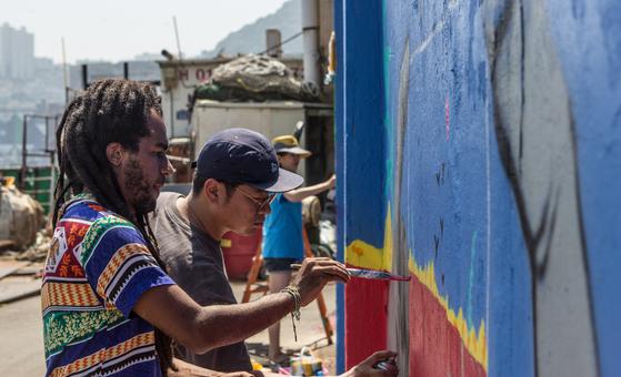 브라질의 아티스트 데리러 제 팰리토(32·왼쪽)씨가 도시재생 사업이 진행 중인 부산 영도구 대평동 쌈지공원에서 지난달 31일 벽화작업에 참여해 색칠하고있다.[송봉근 기자]