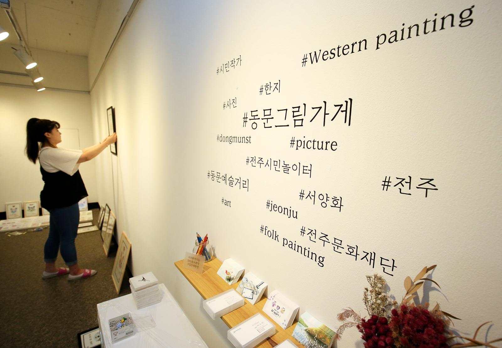 지난 9일 전주시민놀이터 1층 갤러리 공간에서 일러스트 작가 박소연(27·여)씨가 그림을 벽에 진열하고 있다. 프리랜서 장정필