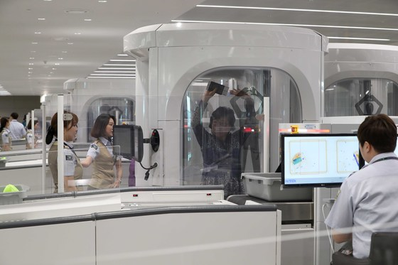 여성 가상 탑승객이 전신검색대 안에 들어가자 여자 검색요원이 모니터를 통해 탑승객 신체 정보를 확인하고있다. 앉아있는남성 검색요원은 탑승객의 짐을 살피고 있다. [중앙포토]