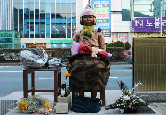 부산 일본영사관 앞에 설치된 소녀상에 시민들이 가져다 놓은 꽃들이 놓여 있다. 송봉근 기자