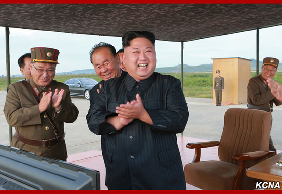김정은 북한 노동당 위원장이 지난 15일 평양 순안 공항 활주로에 마련된 관람석에서 화성-12형 미사일 발사 직후 미사일 개발 책임자들과 박수를 치고 있다. 북한은 화성-12형에 핵탄두 장착이 가능하다고 주장하고 있다. [사진 조선중앙통신]