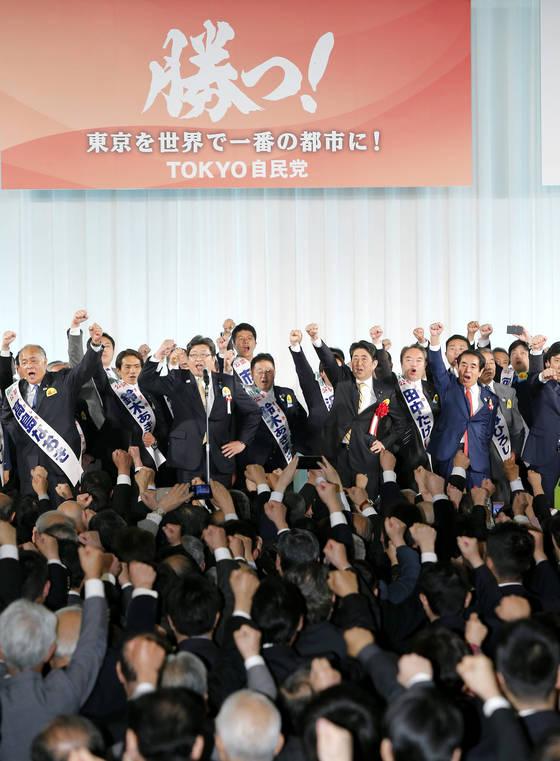자민당 총재인 아베 신조 총리(가운데)가 지난 4월 11일 열린 도쿄도의회 선거 결기대회에서 당 간부ㆍ입후보자들과 주먹을 불끈 쥐고 승리를 다짐하고 있다. [지지통신]