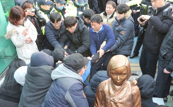 지난 12월 28일 부산 일본영사관 앞에서 부산 동구청 철거반원들에 의해 소녀상 설치 추진 시민단체 시위자들이 끌려나가고 있다. 송봉근 기자