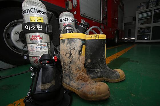 화재 진압 중 순직한 고 이영욱 소방위와 이호현 소방사가 17일 현장에서 착용했던 안전화와 공기호흡기가 강릉소방서 경포안전센터에 놓여 있다. [뉴시스]