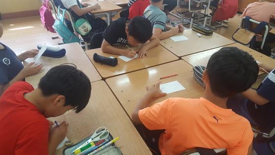 두 귀가 없는 유기견 '꽃님이'에게 편지를 쓰는 학생들. 최은경 기자