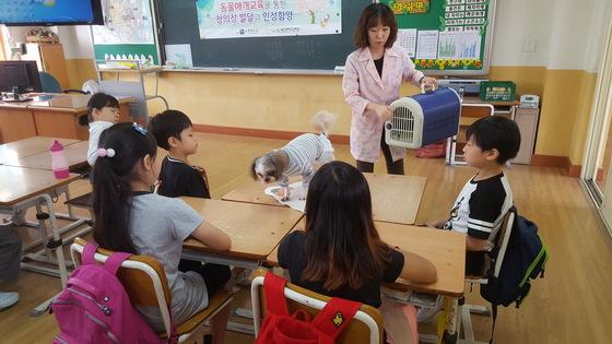 '꽃님이'의 등장. 학생들이 강아지가 놀랄까 봐 소리를 지르거나 함부로 만지지 않고 조용히 눈만 맞추고 있다. 최은경 기자