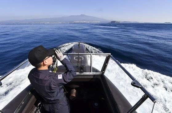 수상항해 중 함교탑에서 함교당직사관이 쌍안경을 이용해 항로상 이상유무를 확인하고 있다. [사진 해군]