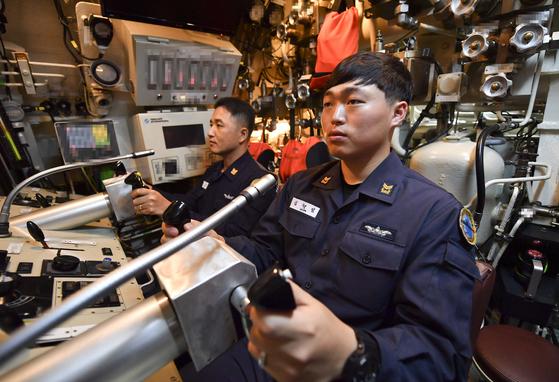 잠항항해 중 함수·미 수평타, 수직타 조종을 위해 타수는 2인1조로 운영된다. 1타수(왼쪽)는 심도 및 침로를, 2타수(오른쪽)는 함의 자세각을 조종한다. [사진 해군]