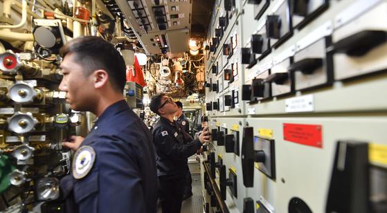 잠수함 승조원들이 조종실(오른쪽)에서 입항을 위해 추진전동기 사용을 준비하고 있다. [사진 해군]