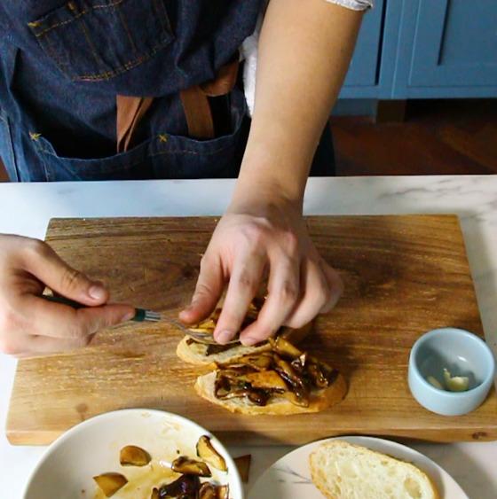 마늘 바른 빵에 버섯 볶음을 올리고 엑스트라 버진 올리브 오일을 뿌려 마무리한다.