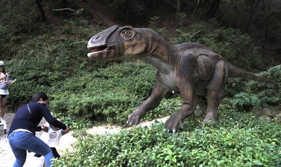 백악기 후기에 살던 마이아사우라. 어미도마뱀이라는 명칭이다. 엄마는 공룡 앞에선 아이사진을 찍고 싶고 아이는 무서워서 다가서지 않는다. 덕평공룡수목원=최승식 기자