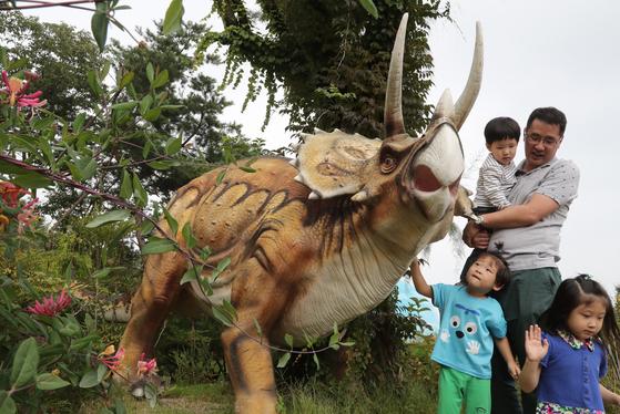 후기 백악기에 살던 트리케라톱스. 사납게 생긴 외모와는 달리 초식공룡이다. 머리에 세개의 뿔이 있는 것이 특징이다. 수목원을 찾은 가족들이 기념사진을 찍고 있다. 덕평공룡수목원=최승식 기자