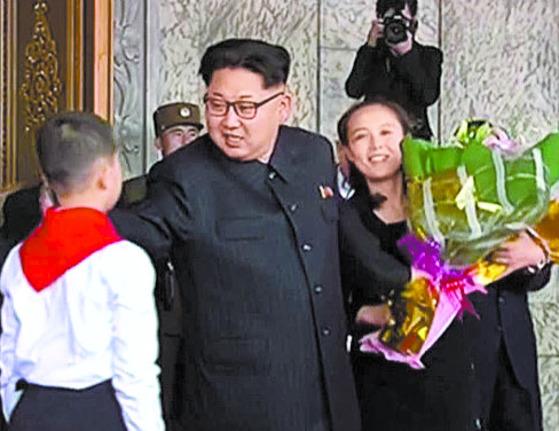 김정은 위원장이 받은 꽃다발을 김여정이 챙기는 모습.  [노동신문]