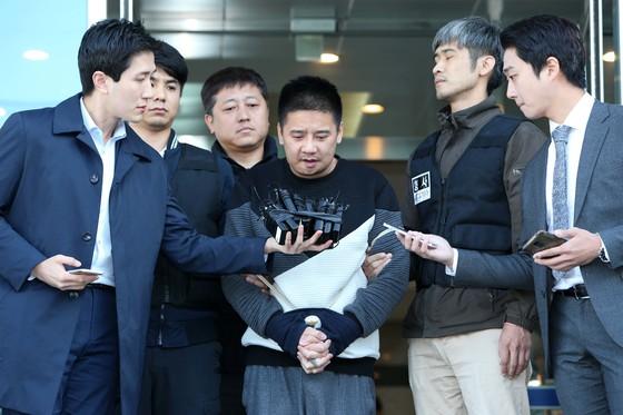 서울 중랑경찰서는 13일 '어금니 아빠' 이영학(35)씨의 얼굴을 공개했다. 경찰은 이씨에게 마스크도 씌우지않았고 수갑 찬 손목도 가리지않았다.이씨는 이날 오전 중랑경찰서에서 기자들의 질문에 답한뒤 호송됐다.20171013.조문규 기자