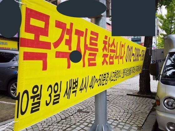 경남 창원시 한 모텔 앞에 설치된 추락 당시 목격자를 찾는다는 내용의 현수막 모습. 위성욱 기자