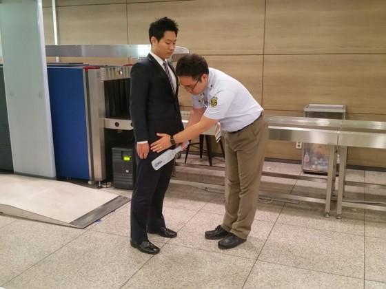 남성 검색보안요원이 금속탐지기와 손을 이용해 남자 탑승객을 검색하고 있다. [사진 인천공항공사]
