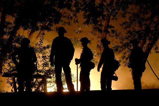 캘리포니아 북부의 칼리스토가 인근에서 산불을 진화하던 소방관들이 맹렬히 번지는 산불을 손놓고 바라보고 있다. [AFP=연합뉴스]