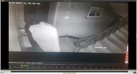 CCTV에 찍히지 않으려고 이불을 뒤집어 쓴 채 건물 안으로 들어가는 김모(23) 씨의 모습. [사진 부산경찰청]