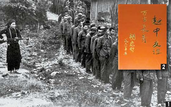 1979년 전쟁 때 중국군 포로들을 베트남 여성 민병대원이 총을 들고 감시하고 있다. 중앙포토. 호찌민의 휘호 越中友誼 중국과 우의.
