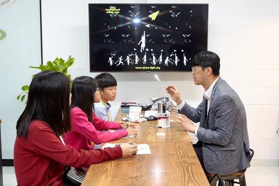 서울새활용플라자에 입주한 쉐어라이트의 박은현 대표를 만나 설명을 듣고 있는 소년중앙 학생기자들.