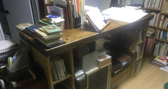 서재 한가운데를 차지하고 있는 두툼한 원목 책상. 서서 일하기 편한 높이다.