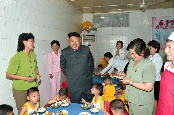 지난 2014년 김정은이 고아 보호시설인 평양애육원을 방문해 관계자들의 설명을 들으며 웃고 있다. .[노동신문]
