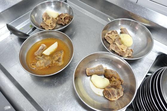 1인분씩 그릇에 담아 놓은 꼬리 토막과 감자 덩이. 여기에 데친 대파를 듬뿍 올리고 끓는 국물에 7~8차례 토렴하면 꼬리찜이 완성된다.