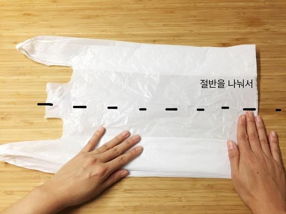 정리할 비닐봉지를 바닥에 모양대로 잘 편다. 세로 절반을 가늠한 후에 양쪽 끝을 안쪽으로 모아 접는다.