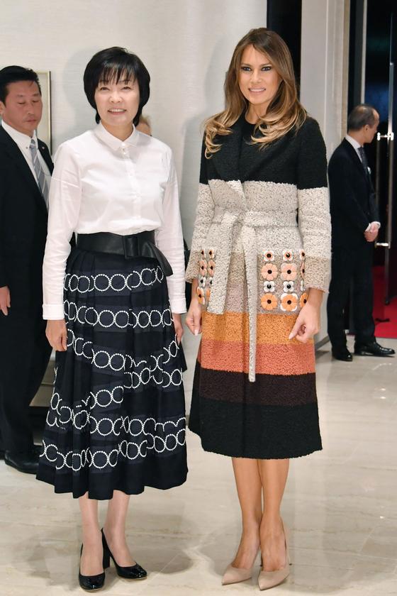 일본 순방 당시 도쿄 긴자의 미키모토 매장에서의 멜라니아 패션. 화려한 배색이 돋보이는 코트에 베이지색 마놀로 블라닉 힐을 매치했다. [연합뉴스]