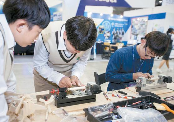 지난해 10월 경기도 고양시 킨텐스에서 열린 '행복교육 박람회'를 찾은 학생들이 나무샤프펜슬 만들기 체험을 하고 있다.