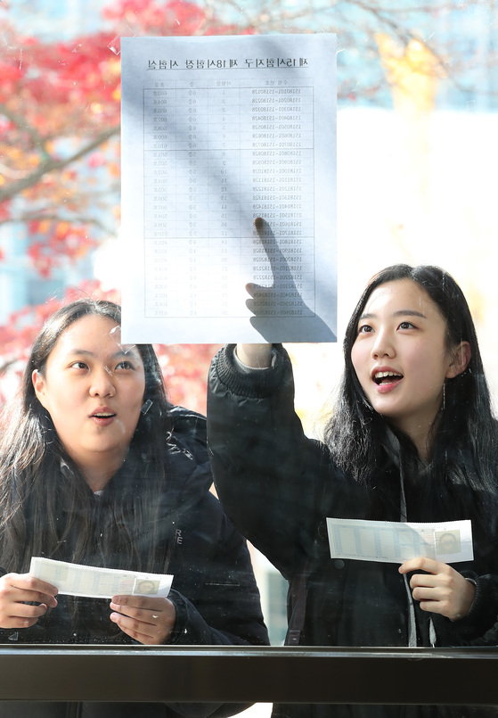 서울 정동 이화여고에서 수험생들이 수험표를 들고 시험실 배치표를 확인하고 있다. 우상조 기자
