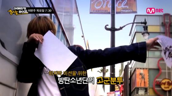 전단지를 돌리는 방탄소년단. [사진 Mnet 방송화면]