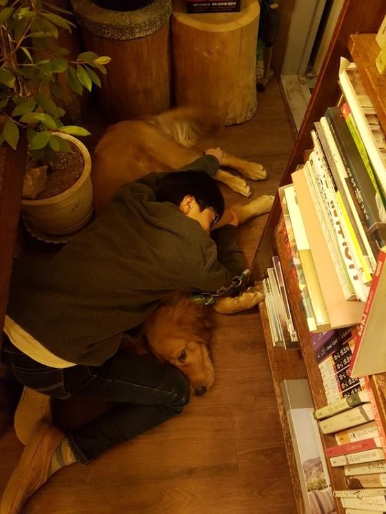 둘째 아들이 개와 실컷 놀고는 피곤한지 개를 껴안고 쉬고 있다.