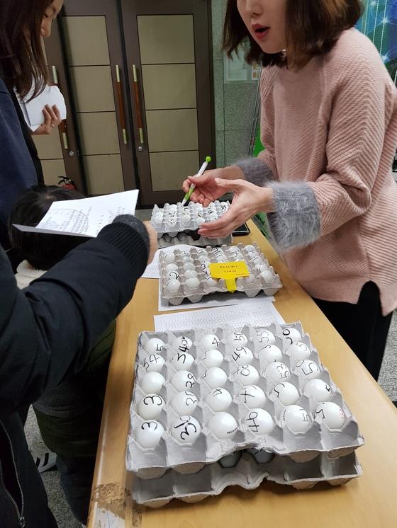 마포구 '유아영어스포츠단' 직원들이 학부모를 상대로 추첨용 탁구공에 적힌 응시 번호를 확인하고 있다.
