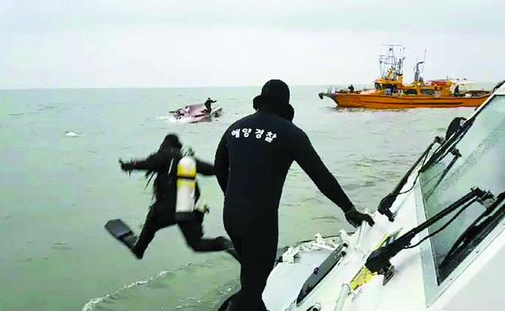 해경이 뒤집힌 배안에 남은 사람들을 구조하기 위해 바다로 뛰어들고 있다.[사진 해경]