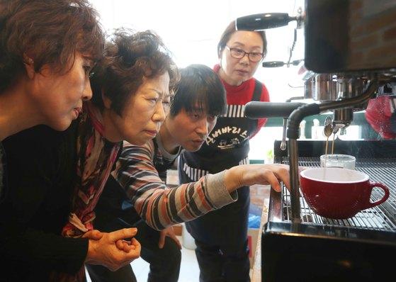 """""""모르는 것을 알아가는 게 너무 신기하고 가슴이 떨리네요"""" 안봉순(65.왼쪽 둘째) 씨가 서울시 중랑구 상봉 1동 주민센터 교육장에서 정재민 강사로부터 커피 내리는 과정을 익히고 있다. 김상선 기자"""