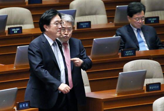 5일 내년도 예산안 표결을 위해 열릴 예정이던 국회 본회의가 자유한국당 의원들 불참으로 정회됐다. 더불어민주당 우원식·국민의당 김동철 원내대표(왼쪽부터)가 의장석으로 가며 이야기하고 있다.