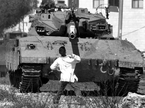 이스라엘군의 탱크에 돌멩이를 던지는 팔레스타인 소년. 분노와 저항의 표현이다.  [사진제공=니케북스]