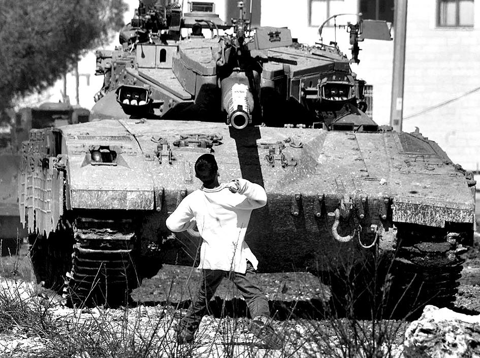 2000년 인티파다 당시 한 팔레스타인 청소년이 예루살렘에서 이스라엘 군의 메르카바 전차 앞에서 물러서지 않고 돌을 던지고 있다. [중앙포토]