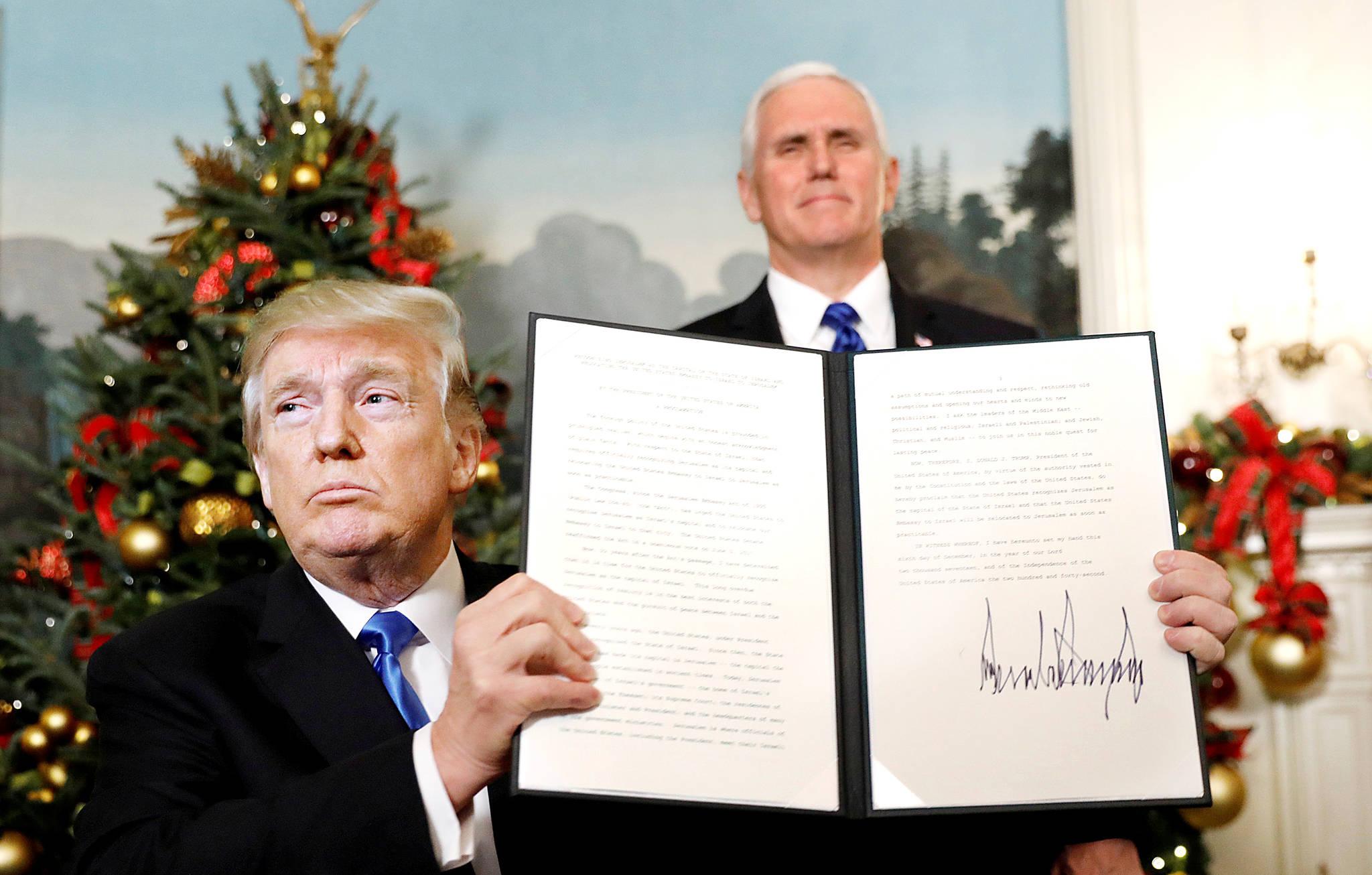 도널드 트럼프 미국 대통령(왼쪽)이 지난 6일 백악관에서 예루살렘을 이스라엘의 수도로 인정하고 현재 텔아비브에 주이스라엘 미국 대사관을 예루살렘으로 옮기는 내용의 선언에 서명한 뒤 이를 내보이고 있다. 오른쪽은 마이크 펜스 미국 부통령. 트럼프의 이 결정은 중동에 피바람을 몰고 올 전망이다 .[로이터=연합뉴스]