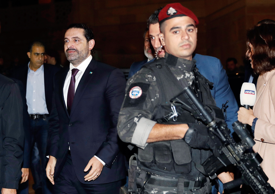 Lebanese Prime Minister Saad Hariri, center, escorted by his bodyguards walks to pray over his father's grave, upon his arrival to Beirut, Lebanon, Tuesday, Nov. 21, 2017. Hariri has returned to Beirut more than two weeks after announcing while in Saudi Arabia that he had resigned his post. (AP Photo/Hussein Malla)
